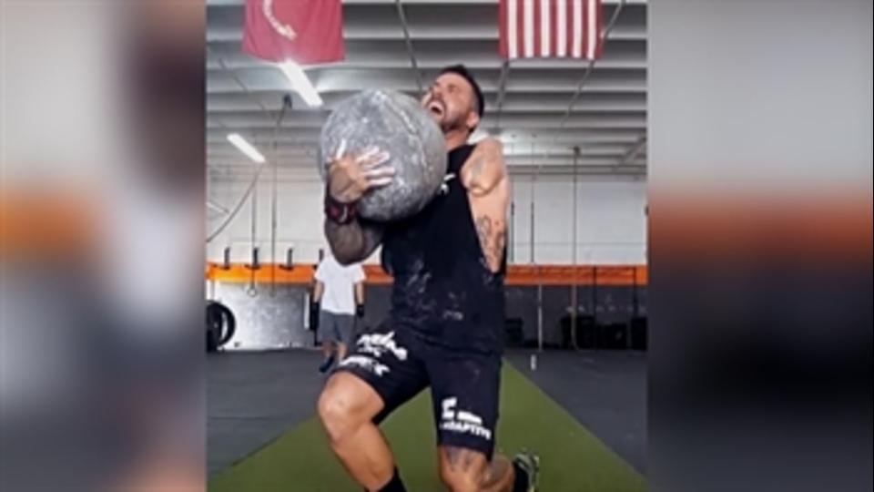 An Army veteran lifts a heavy stone