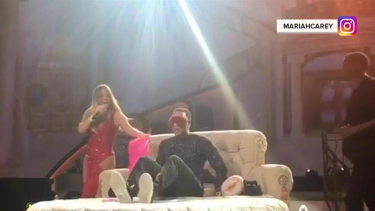 Mariah Carey blindfolds. tickles John Legend on stage