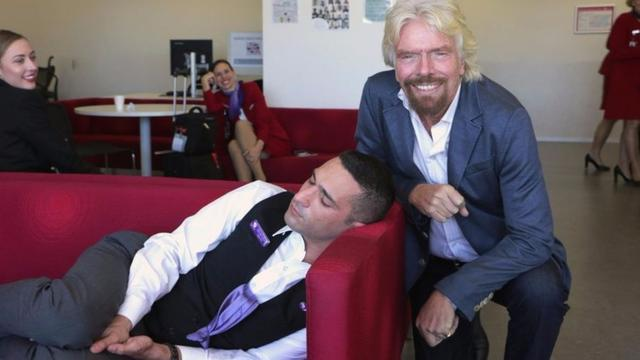 Richard Branson Has His Photo Taken With A Sleeping Employee